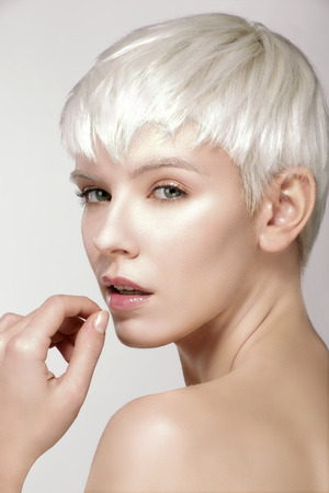 girl short hair: Beauty model blonde short hair showing perfect skin  on white Stock Photo