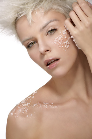 blond model applying a scrub treatment on the body an face white background