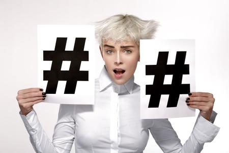 Modelo rubia muy mostrando dos signo hashtag en papel fondo blanco Foto de archivo - 36360384