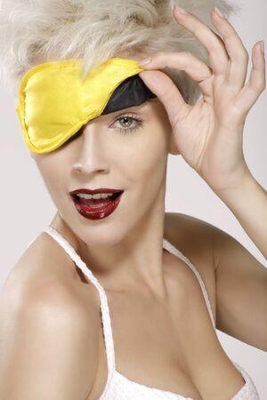 eye mask: beautiful smiling model wearing a yellow sleep mask  on white