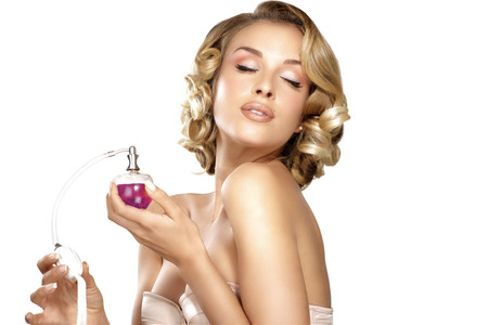 parfume: Young woman applying perfume on her neck space for text on white