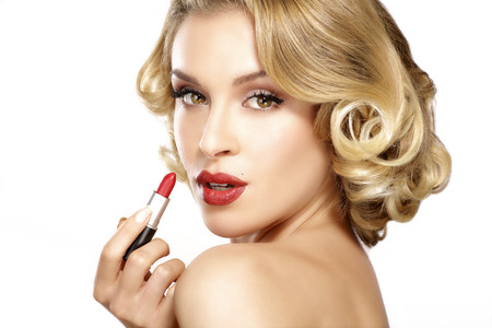 Beautiful young blond model curly hair applying lipstick on white