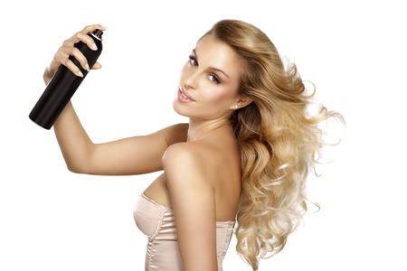 bella modelo aplicando spray en el pelo ventoso sobre fondo blanco Foto de archivo