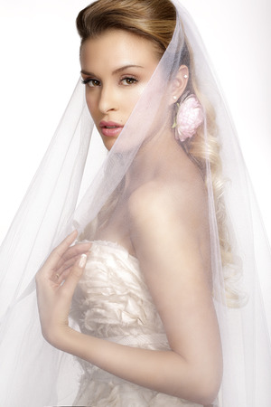 bridal makeup: portrait of  young woman in wedding dress posing with  bridal veil on white