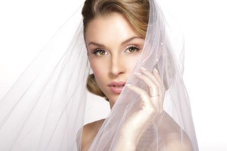 Porträt der jungen Frau im Hochzeitskleid posiert mit Brautschleier auf weiß