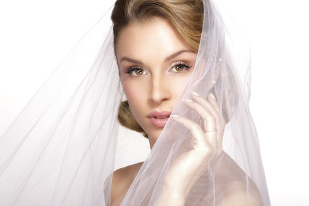 bridal hair: portrait of  young woman in wedding dress posing with  bridal veil on white