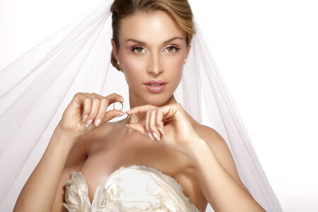 bridal veil: portrait of  young woman in wedding dress posing with  bridal veil on white