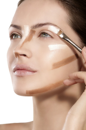 Beautiful model applying foundation with a brush on white