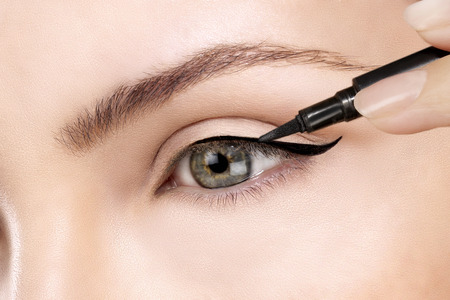 line up: model making eyeliner on eye  closeup Stock Photo