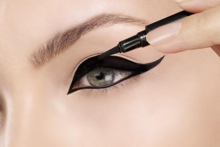mujer maquillandose: modelismo delineador en los ojos de cerca