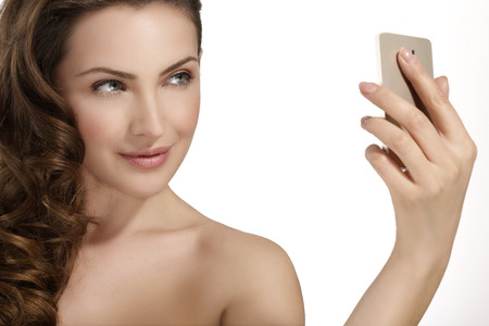 beautiful woman take a smiling selfie with smartfone on white