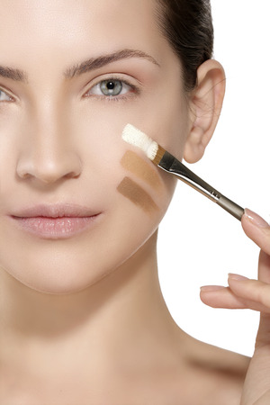 eye cream: Beautiful model applying foundation with a brush on white