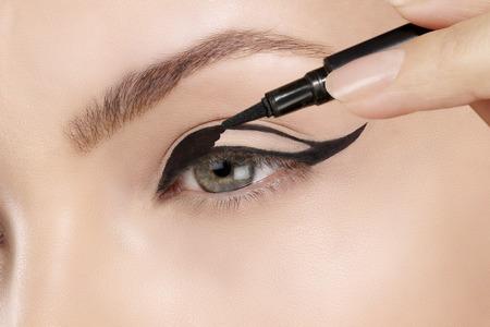 make up brushes: model making eyeliner on eye  closeup Stock Photo