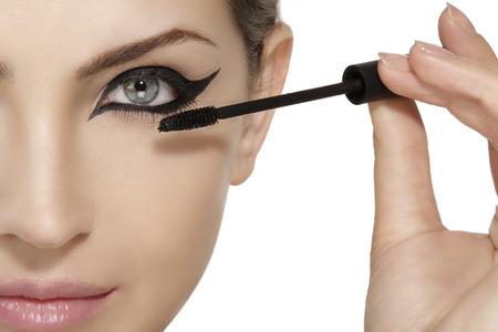Beautiful model applying mascara on eyelashes  close up on white
