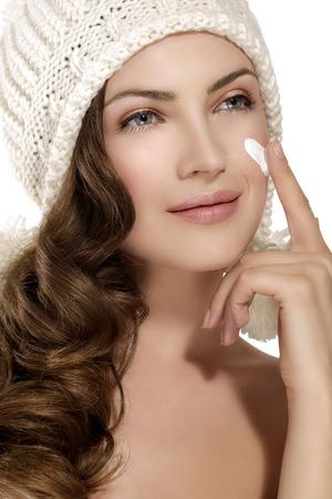 frio: bella modelo aplicando una crema en la cara del frío invierno en blanco Foto de archivo