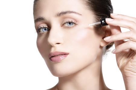 bella modelo aplicando un tratamiento con suero piel en blanco