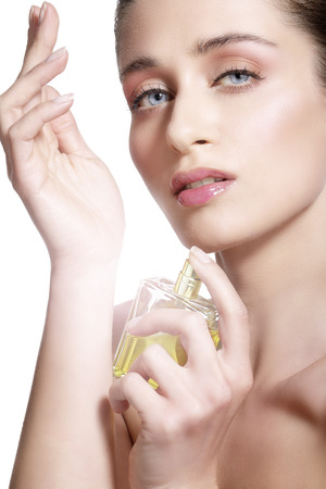 Beautiful young model spraying a flowers fragrance on her body photo