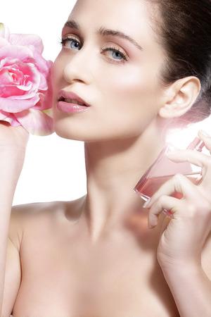 mujer con rosas: Modelo joven hermoso rociar una fragancia de flores sobre su cuerpo Foto de archivo
