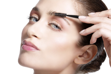 Closeup beautiful woman with eyebrow brush tool  on white