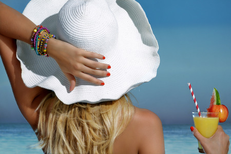 Elegant beautiful woman refreshing on the beach looking the sea Standard-Bild