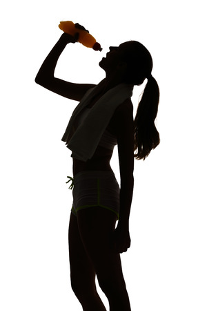 one woman: one woman exercising fitness drinking energy drink in silhouette on white background Stock Photo