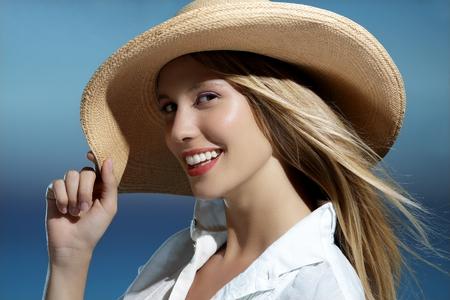 Natuurlijk blond meisje lachend een hoed dragen op het strand blauwe lucht Stockfoto