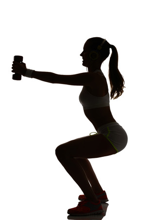 lunges: one woman exercising fitness workout lunges crouching weight training in silhouette on white background Foto de archivo