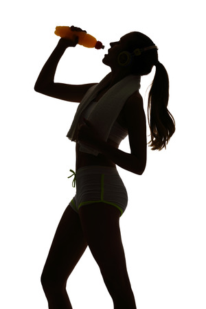 energy drink: one woman exercising fitness drinking energy drink in silhouette on white background Stock Photo