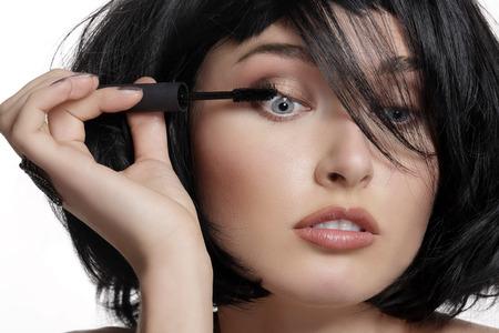 makeup eyes: Young beautiful woman applying mascara makeup on eyes by brush on white Stock Photo