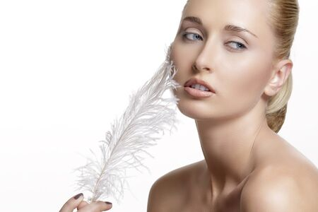 white feather: Retrato de la muchacha hermosa con la pluma blanca en la cara en blanco