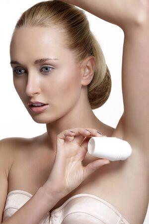 beautiful armpit: beautiful woman applying roll deodorant on white