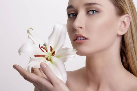 beauty woman: Beauty blonde young woman showing a fresh flower on white