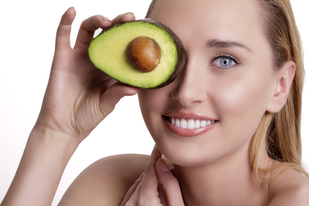 young woman face: young happy woman showing an avocado  on white