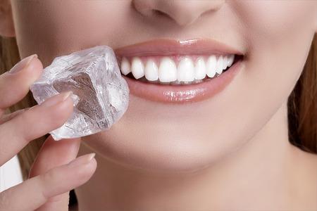 Closeup of beautiful woman biting an ice cube on white Stock Photo