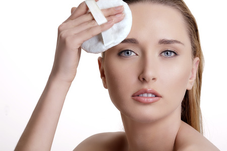 model face: Beautiful model applying powder on her face  on white