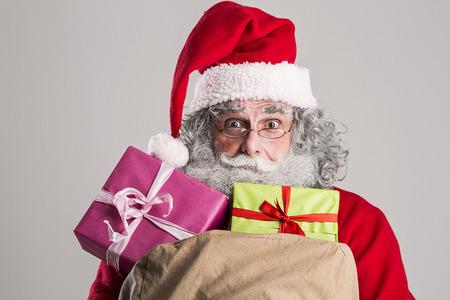 weihnachtsmann lustig: cheerful funny traditional santa claus with bag Lizenzfreie Bilder