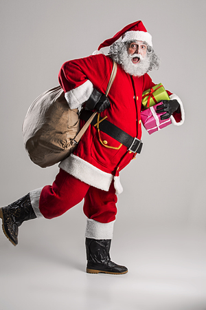 cheerful funny traditional santa claus with bag Stock Photo
