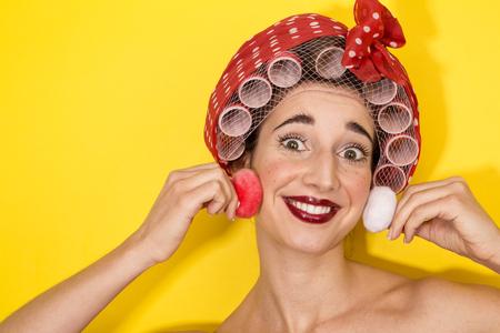 funny housewife applying makeup on yellow
