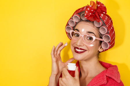 funny happy girl vintage style applying cream on face on yellow