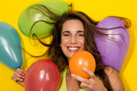 baloons: smiling girl plays with colorful baloons on yellow background Stock Photo