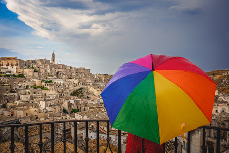 Matera (Italy), September 2017. Tourist with a rainbow umbrella at the belvedere over the ancient town called