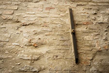 Old metal rod anchor bar on a brick and stone masonry wall.