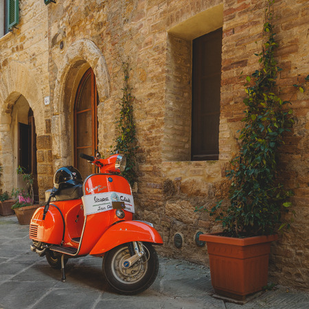 Vintage Vespa Piaggio parked in a street of a Tuscan town. Italy, 2017. Stock Photo - 119470198