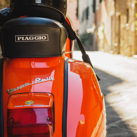 Vintage Vespa Piaggio parked in a street of a Tuscan town. Italy, 2017. Stock fotó - 119470200
