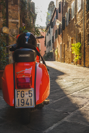 Vintage Vespa Piaggio parked in a street of a Tuscan town. Italy, 2017. Stock Photo - 119470201