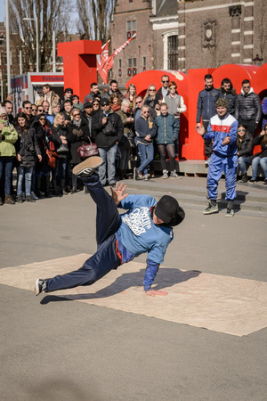 Breakdancer performing in Museumplein in Amsterdam (Netherlands). March, 2015. Portrait format.