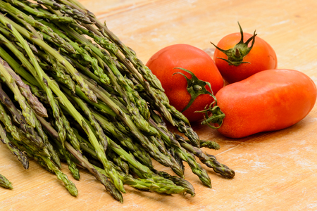 A bunch of asparagus tied with a cord on a wooden chopping board. Close up landscape format 写真素材