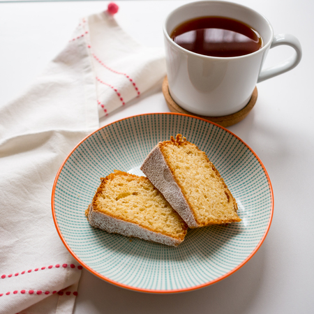 Cup of tea and two slices of sponge cake in a plate on a white table with a white and red tea towel. Top view. Squared format. Stock fotó