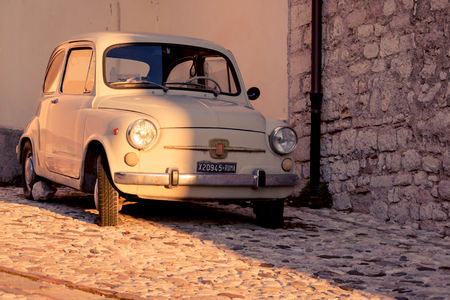 Vintage Fiat 500 parked in the street of a medieval town. Italy, 2011. Landscape format.