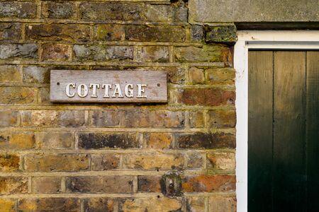 Cottage wooden sign on a brick wall. Landscape format.